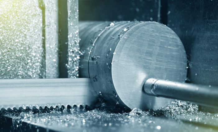 The process of cutting metal with an electric saw in a factory. Electric saw cuts round metal